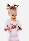 The baby girl with a pacifier in gouache soiled hands and shirt isolated Royalty Free Stock Image