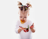 The baby girl with a pacifier in gouache soiled hands and shirt isolated Royalty Free Stock Photography