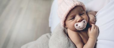 Baby girl with pacifier sleeping. Closeup of face of baby girl with pacifier sleeping stock images