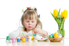Baby girl painting Easter eggs isolated. On white background Stock Photo