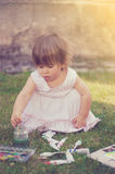 Baby girl painting in yard Royalty Free Stock Images