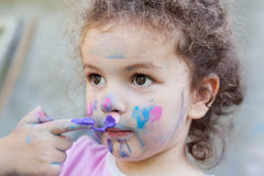 Baby girl paints her face Royalty Free Stock Images