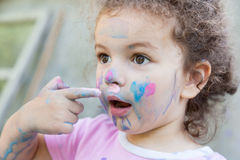 Baby girl paints her face Royalty Free Stock Photography