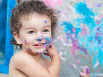 Baby girl paints her face Stock Photos