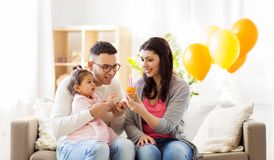 Baby girl with parents at home birthday party. Family, holidays and people concept - mother, father with cupcake and happy little daughter at home birthday party Stock Photography