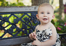 Baby girl on park bench stock photo