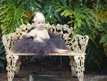 Baby girl on park bench. A one year old baby girl dressed up in tutu and flower headband sitting on bench in the park Royalty Free Stock Images