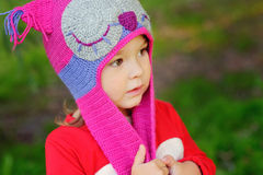 Baby girl in a park in a knitted hat owl Stock Images