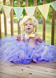 Baby girl at party. Baby girl on an outdoor patio decorated for a party wearing a tutu and flower bonnet royalty free stock photos