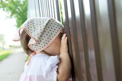 Baby girl peeping through hole in fence. Child looking. On something royalty free stock images