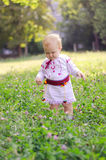 Baby girl picking flowers. Baby girl in ethnic dress picking flowers in meadow stock images