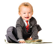 Baby Girl on Pile of Money Stock Photo