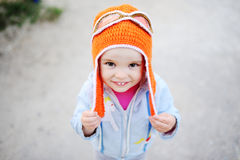 Baby girl in pilot hat smiling at the camera. Dream of flying Royalty Free Stock Image
