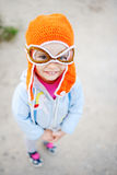 Baby girl in pilot hat smiling at the camera. Dream of flying Royalty Free Stock Photography