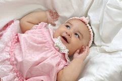Baby Girl in Pink 6 months. Cute 6 month old hispanic baby girl in a pink dress lying in a crib Stock Images