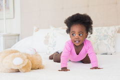 Baby girl in pink babygro crawling on bed. At home in the bedroom stock photography