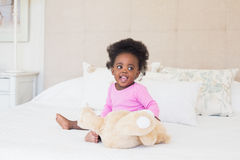 Baby girl in pink babygro sitting on bed. At home in the bedroom royalty free stock image