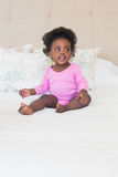 Baby girl in pink babygro sitting on bed. At home in the bedroom stock photos