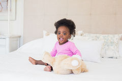 Baby girl in pink babygro sitting on bed. At home in the bedroom royalty free stock photo