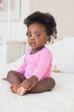 Baby girl in pink babygro sitting on bed Stock Photos
