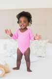 Baby girl in pink babygro standing on bed. At home in the bedroom stock images
