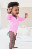 Baby girl in pink babygro standing on bed. At home in the bedroom stock image