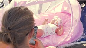 Baby girl in pink bassinet and mother browsing web on cell outdoor. Woman browsing social network on cell phone being outdoor with baby daughter lying in pink stock video