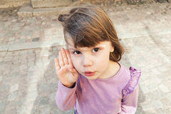 Baby girl in pink blouse speaks quietly Royalty Free Stock Photo
