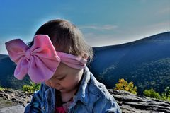 Baby girl with pink bow on mountain royalty free stock photos