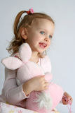 Baby girl and pink bunny Stock Photos