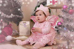 Baby girl with pink butterfly wings sitting under Christmas tree Stock Photography