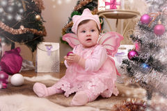 Baby girl with pink butterfly wings under Christmas tree Stock Photography