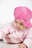 Baby girl with pink cap lying down. Close up of baby girl with pink cap lying down on wooden floor  looking away and playing.Check also Children Royalty Free Stock Images