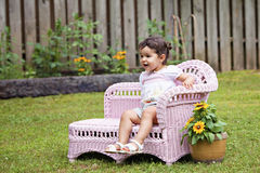 Baby girl in pink chaise lounge Stock Photos