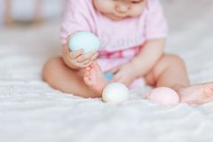 Baby girl in pink clothes play with colour eggs on bed easter. Little baby child, baby girl, playing with bunnies and easter eggs at home, colorful hand drawings stock image