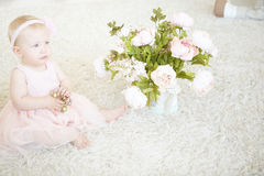 Little baby girl sitting on a carpet with necklace and flower in Stock Photo