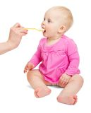 Baby girl in pink dress eats from spoon Stock Image