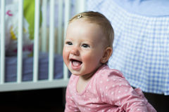 Baby girl in pink dress at home sitting on the floor, smiling. Cute little baby girl in pink dress at home in her bedroom, sitting on the floor, smiling stock image
