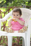 Baby girl in pink eating pear Royalty Free Stock Photography