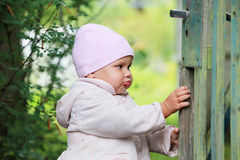 Baby girl in pink hat plays with old green gate Stock Images