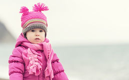Baby girl in a pink hat and scarf Stock Images