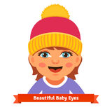 Baby girl in pink hat smiling and watching Stock Photo