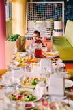 Baby girl in pink in highchair in front of big fest table at birthday party stock photos