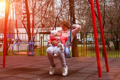 Baby girl in pink jacket with her mom on coral hoodie on a swing at sunny spring day.  royalty free stock photography