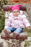 Baby girl in pink jacket sitting on wooden chair Stock Photo