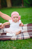 Baby girl in pink knitted hat sitting on a rug in the park Stock Photos
