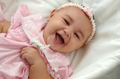 Baby Girl in Pink Laughing. Closeup portrait of an adorable infant girl in a pink dress stock images