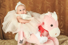 Baby girl on a pink poney Royalty Free Stock Photos