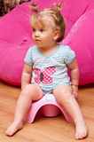 Baby girl on pink potty royalty free stock photography