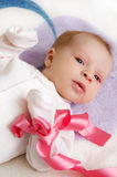 Baby girl with pink ribbon Royalty Free Stock Images